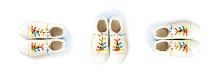 Three pairs white sneakers with rainbow laces for the child on a isolated backgroun. Top view.