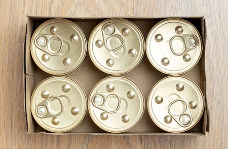 Jars of cat food in a box. Packaging on wooden background.