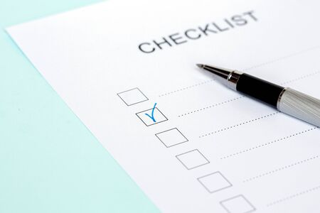 Close-up of on Checklist with pen on a blue background.