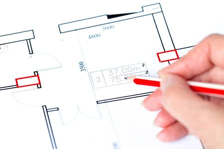 Macro close up of quantity surveyors hand reviewing technical drawing. Architect working on blueprint