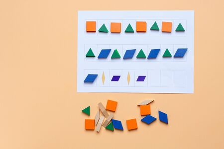 A game. Lay out wooden blocks according to the shape, color indicated in the table. The development of thinking, attention, quick wit, imagination. Standard-Bild
