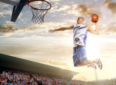 canestro basket: Giocatore di pallacanestro in azione su sfondo di cielo e di folla Archivio Fotografico