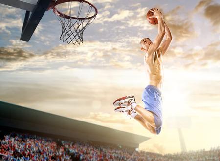 空と群衆の背景のアクションのバスケット ボール選手