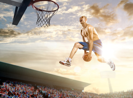 background basketball court: Basketball player in action on background of sky and crowd