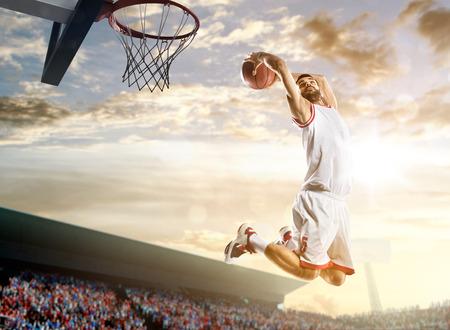空と群衆背景にアクションのバスケット ボール選手