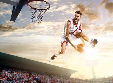 hombre disparando: El jugador de baloncesto en la acción en el fondo del cielo y multitud