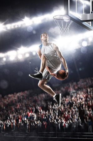 basket: Basketball player in action flying high and scoring Stock Photo