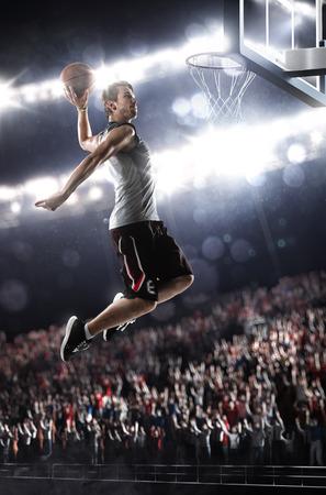 cancha de basquetbol: El jugador de baloncesto en la acción volando alto y anotando Foto de archivo