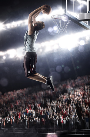 Basketball player in action flying high and scoring Stock Photo