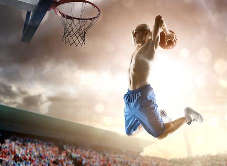 El jugador de baloncesto en la acción en el fondo del cielo y multitud Foto de archivo - 28789134