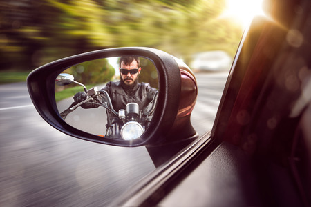 Biker in rear view mirror Imagens