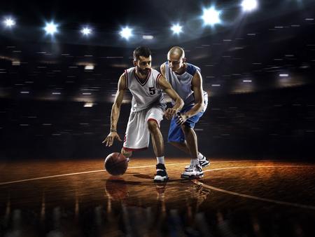 Twee basketbal spelers in actie in de gymzaal in lichten