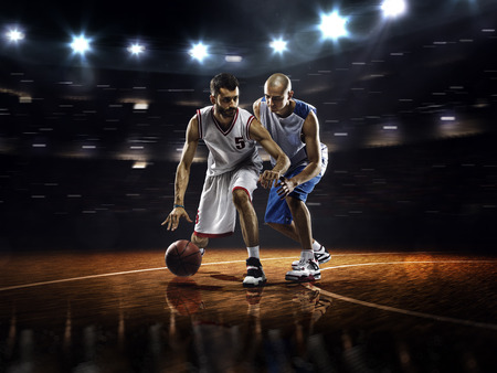 basketball team: Two basketball players in action in gym in lights Stock Photo