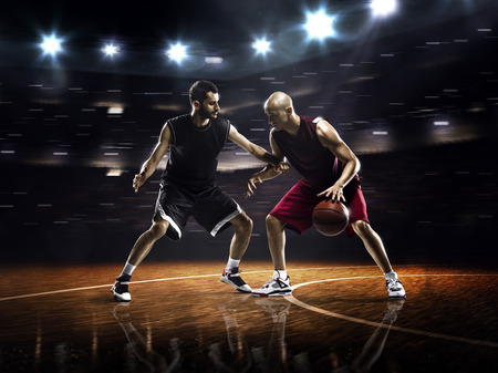 Two basketball players in action in gym in lights photo