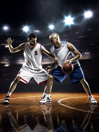 action shot: Two basketball players in action in gym in lights Stock Photo