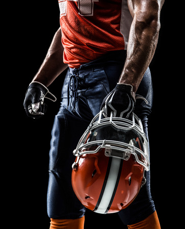 casco rojo: Jugador deportista de fútbol americano está aislado en el negro Foto de archivo