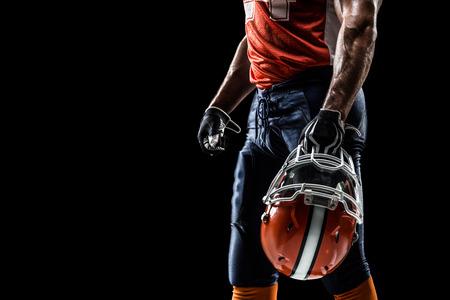 uniforme de futbol: Jugador deportista de fútbol americano está aislado en el negro Foto de archivo