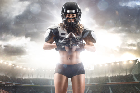 american football helmet: American football female player posing with ball