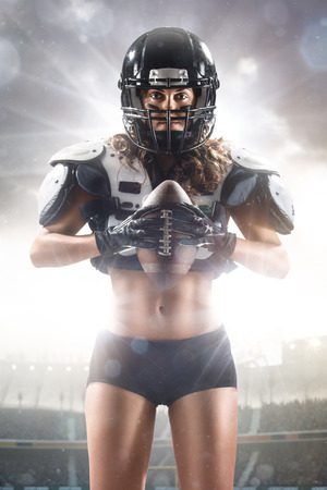 sports uniform: American football female player posing with ball