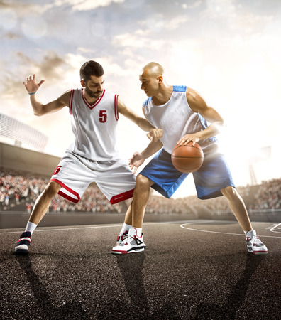 Basketball players in action on sky and crowd Stock Photo