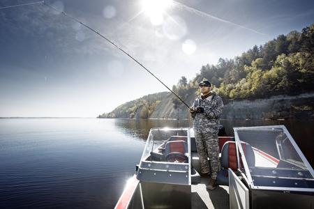 Men is de visserij op de bas boot Stockfoto