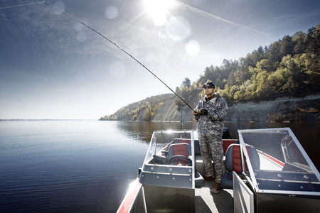 freshwater fish: Men is fishing on the bass boat Stock Photo