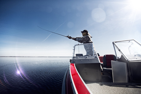 Men is fishing on the bass boat photo