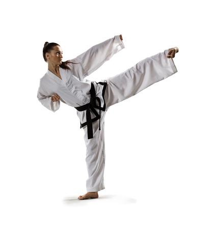 patada: Mujer karate en la acci�n aislada en blanco Foto de archivo