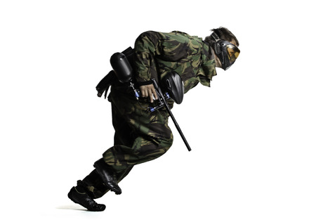 Isolated on white painball player in action