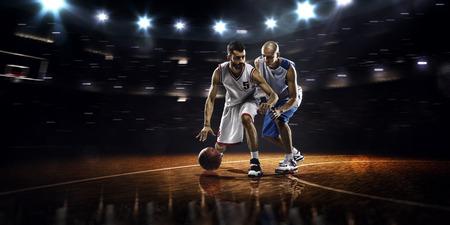 canestro basket: Due giocatori di basket in azione in palestra a luci
