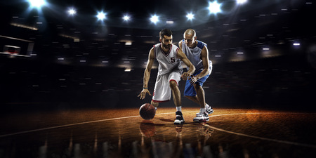 Two basketball players in action in gym in lights Stock Photo