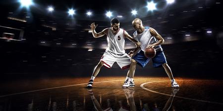 pelota: Dos jugadores de baloncesto de acci�n en el gimnasio en las luces Foto de archivo