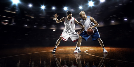 ball: Two basketball players in action in gym in lights Stock Photo