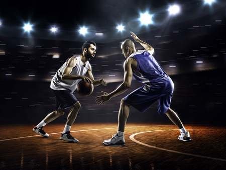 Two basketball players in action in gym in lights Stock fotó
