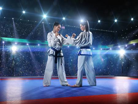 Twee professionele vrouwelijke karate strijders vechten op de grote arena