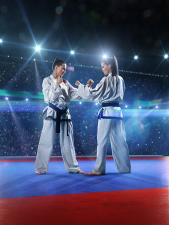self  discipline: Two professional female karate fighters are fighting on the grand arena Stock Photo