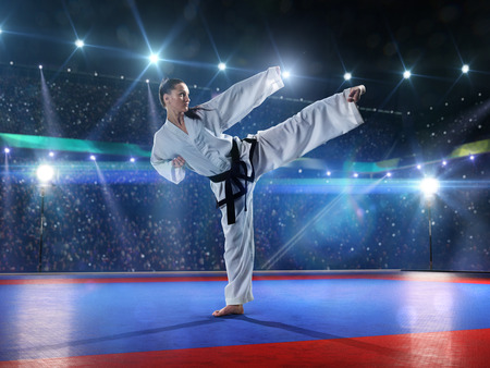 martial: Professional female karate fighter is fighting on the grand arena