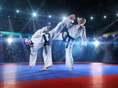 female kick: Two professional female karate fighters are fighting on the grand arena Stock Photo