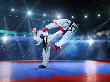fight arena: Two professional female karate fighters are fighting on the grand arena Stock Photo