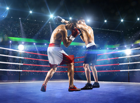 Two professionl boxers are fighting on the grand arena