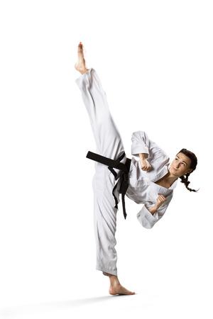 patada: Profesional karateca femenino aislado en el fondo blanco