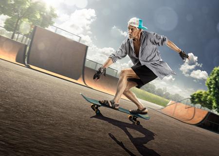 De oude man is schaatsen op skateboard in skatepark