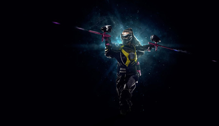 gamer: Female paintball player is playing the game in the dark