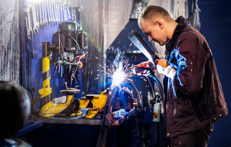 automobile workshop: Mechanical carefully welding the tube by  electric arc