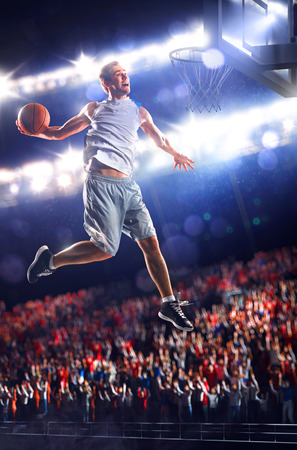 Basketball player in action is flying high and scoring Imagens