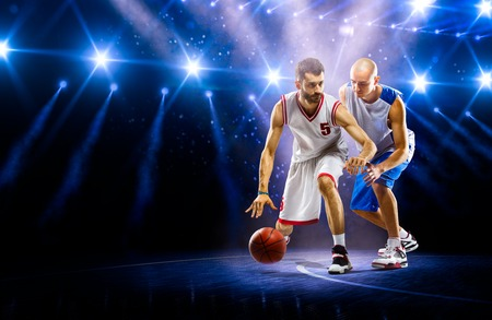 basket: Two basketball players in action in gym in lights Stock Photo
