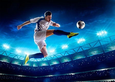 uniforme de futbol: Jugador de fútbol en acción sobre fondo estadio noche