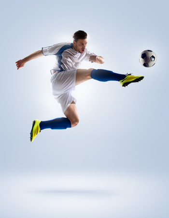 kicking ball: football soccer player in action  isolated on color background