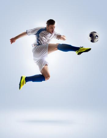 uniforme de futbol: jugador de f�tbol de f�tbol en la acci�n aislada en el fondo de color