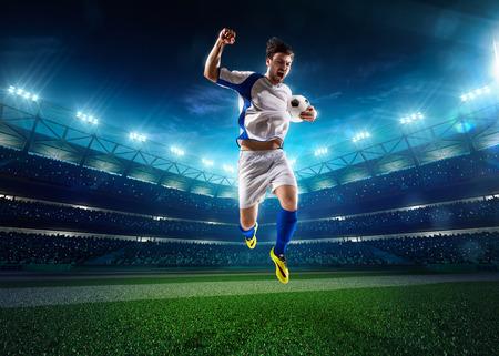 Voetballer in actie op de nacht stadion achtergrond